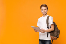 Schoolboy With Backpack Using Tablet Computer And Smiling