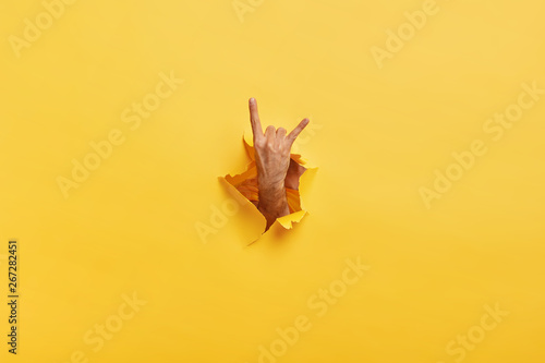Pinturas sobre lienzo  Unrecognizable man makes rock n roll gesture through ripped hole in yellow paper