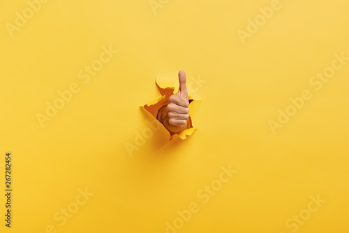 Poster de jardin Individuel Image of unrecognizable man makes thumb up gesture, demonstrates approval or agreement, gestures through torn paper wall yellow background. Body language concept. Hand sign. Hole in wall. Like gesture