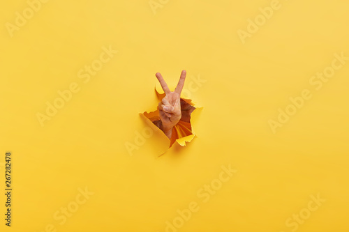 Fotomural  Shot of unrecognizable man demonstrates victroy sign through torn hole in yellow paper, expresses celebration and triumph