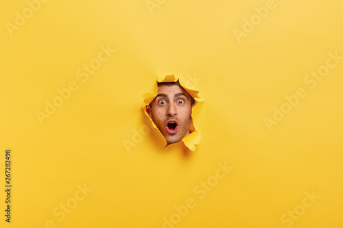 Fotografía Surprised young man with bristle keeps mouth widely opened, stares through torn paper wall, shows only face, expresses wonder and disbelief, poses against yellow background