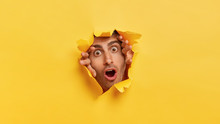 Stupefied Dark Eyed European Man Tears Yellow Paper, Stares Through Hall With Scared Expression, Notices Something Terrified, Has Widely Opened Eyes And Mouth. Yellow Background. Omg Concept