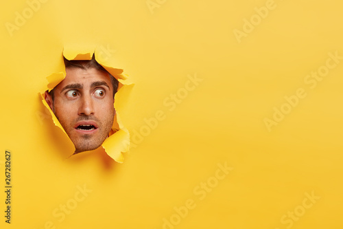 Scared Caucasian man focused aside with surprised facial expression, feels puzzl Fototapeta