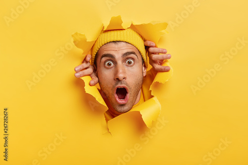Headshot of stupefied young man with European appearance, wears yellow hat, keeps head in torn paper wall, keeps jaw dropped from surprisement, impressed by sudden bad news or rumor Fotobehang