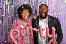 Glad Dark Skinned Couple With Charming Smile, Being Well Dressed, Hold Letter Balloons Meaning Party, Stand Closely, Pose Against Purple Decorated Background With Falling Confetti. Celebration Concept