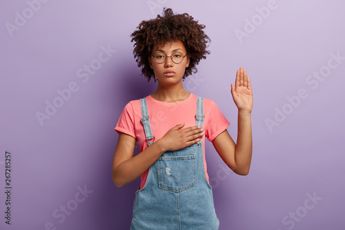 Photo Confident serious woman with curly hair makes sincere promise or oath, keeps one hand on heart, solemnly swears, raises palm, demonstrates loyalty gesture being honest poses against purple background