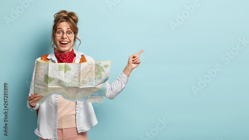 Fototapeta Smiling optimistic young European female guide holds map, shows direction to tourist away, demonstrates destinations of showplace, dressed casually, isolated on blue wall, searches right route obraz