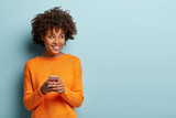 Photo of cheerful delighted African American woman types sms on modern cell phone device, enjoys good internet connection, dressed in orange jumper, focused aside, isolated on blue studio wall