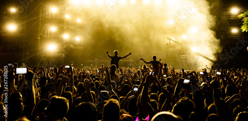 Rear view of fans with smart phones in front of stage at music festival. - 267288015