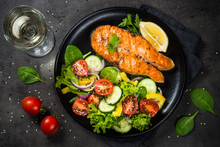 Grilled Salmon Fish Steak With Vegetables On Black.