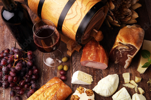 Poster de jardin Inde Still life in a rustic style. Grapes on a wooden table with a bottle of wine and meat and cheese. Antipasto and red wine