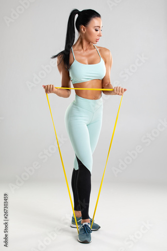 Carta da parati Fitness woman using a resistance band in her exercise routine