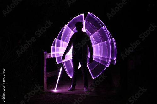 Photo Silhouette of a man standing with a lightsaber with neon drawings and leds at li