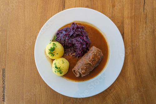 Fotografie, Obraz Rinderroulade, Beef roll or roulades, traditional german meal, thin meat wrap bacon, onion and pickle, serve with pickled red cabbage, dumplings potatoes and sauce on white plate and wooden table