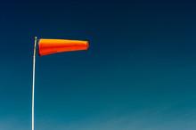 Horizontally Flying Orange Windsock And Clear Dark Blue Sky.