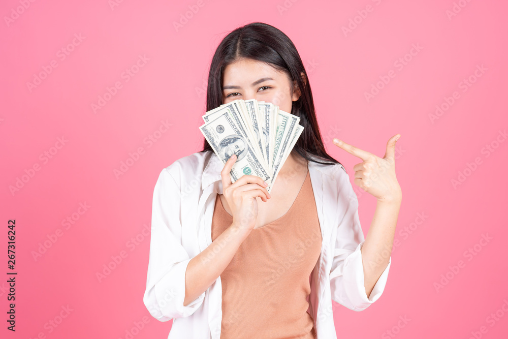 Fototapety, obrazy: Successful beautiful Asian business young woman holding money US dollar bills in hand on pink background , business concept