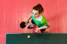 Sixteen-year-old Teen Girl Makes A Serve Of The Ball In Table Tennis, Top View. Teens And Ping Pong