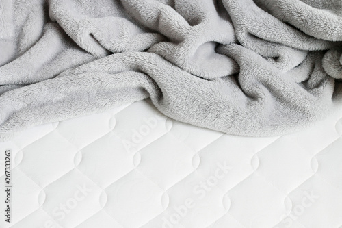 Obraz Grey blanket with pompoms on the new mattress. - fototapety do salonu