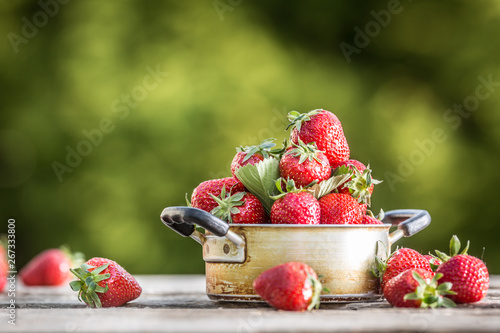 Fresh ripe strawberries in vintage kitchen pot on old garden table