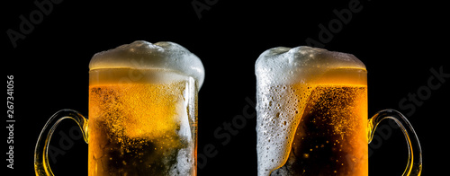 Two large glasses of beer with foam close-up, facing each other, isolated against a black background Wallpaper Mural