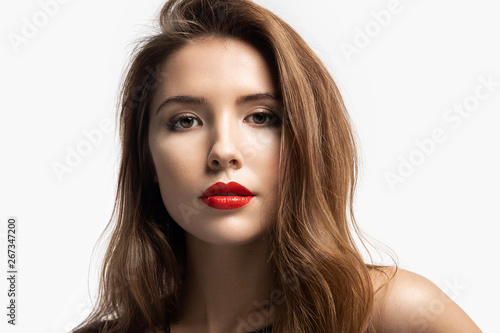 Close-up fashion portrait of beautiful young woman with bright red lips. Charming girl with pretty makeup in studio. Beauty and lifestyle concept. Isolated on white background