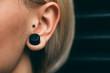 Leinwandbild Motiv Close up of young woman with ear piercings