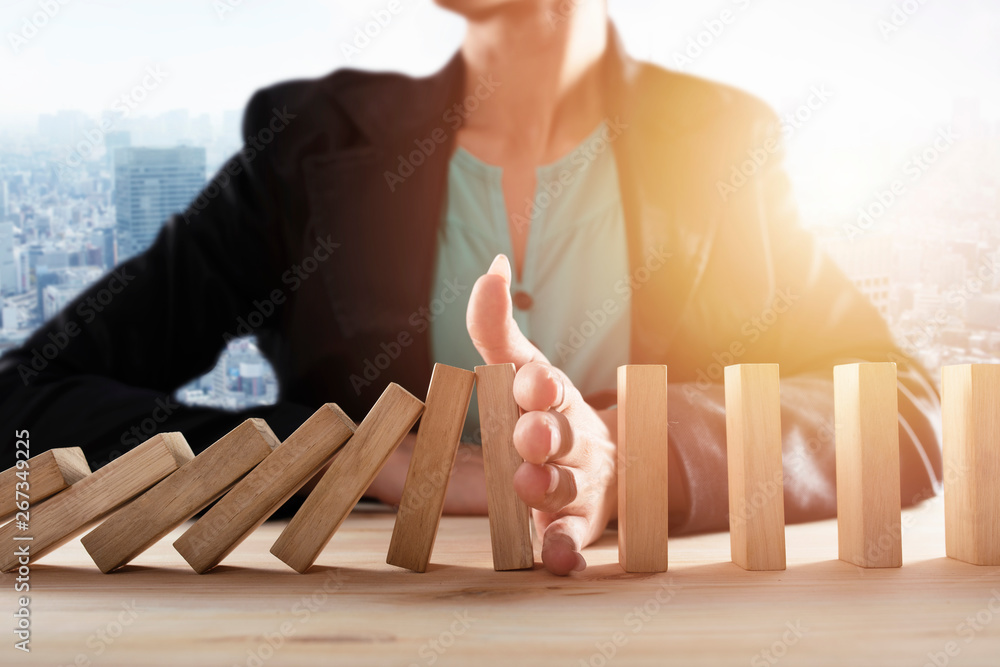 Fototapeta Businesswoman stops a chain fall like domino game. Concept of preventing crisis and failure in business.