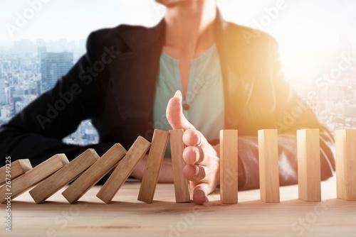 Pinturas sobre lienzo  Businesswoman stops a chain fall like domino game