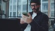 Bearded hipster working process of startup project creating in coworking space. Man wearing eye glasses and using smartphone at office