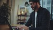 Bearded hipster man wearing eye glasses and using devices at office.Confident busy male freelancer in trendy eyewear using laptop while surfing net searching information for presentation
