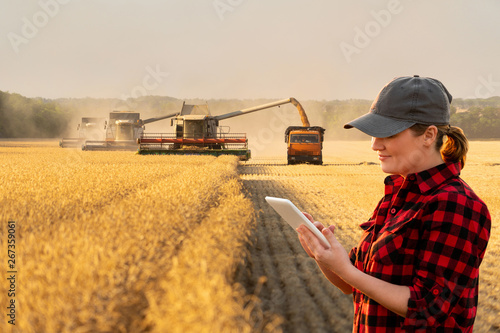 Aufkleber - Woman farmer with digital tablet on a background of harvesters. Smart farming concept.