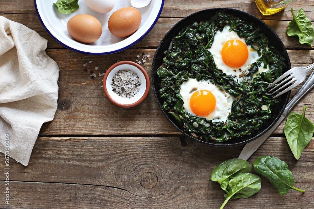 Fototapety, obrazy: Skillet Poached Eggs with Spinach. Overhead view