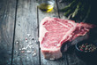 canvas print picture - Raw T-bone Steak with fresh herbs and oil on dark wooden background