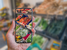 Augmented Reality Grocery Shopping Mobile App. Hand Is Holding Cellphone With AR Application Scanning Vegetables At Food Market.