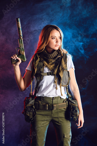 Photo  Calm and concentrated woman soldier possessing such features as battle and stress resistance and good coordination of movements holds gun in hands