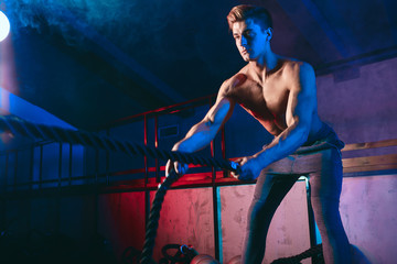 Young muscular male bodybuilder with naked torso doing Fat Burning Battle Rope Finisher Workout in a dark gym.