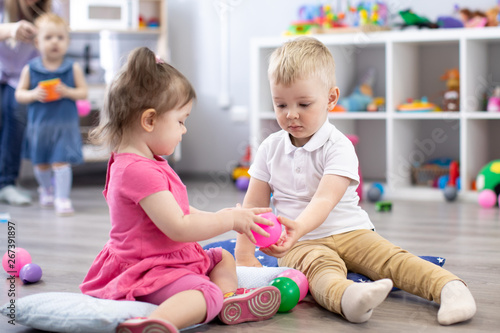 Little toddlers boy and a girl play together in nursery room Wallpaper Mural
