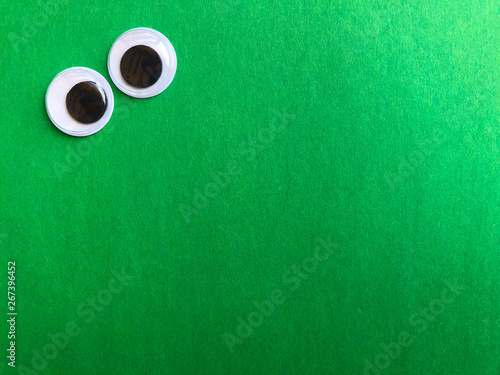 Poster Golf googly eyes on green background with space for text or image