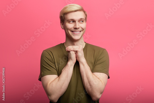 Photo Cunning tricky smiling man standing with hand together , looking aside, over pink background