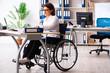 Leinwandbild Motiv Female employee in wheel-chair at the office