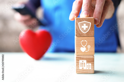 Young man hand arranging wood block stacking with icon healthcare medical, insurance for your health concept medicine on phone.