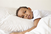 Sadness And Loneliness Concept. Portrait Of Sad Or Thoughtful Pensive Afro American Male Child In White T-shirt Lying Awake On Bed, Feeling Upset Because Of Nightmare, Staring In Front Of Him