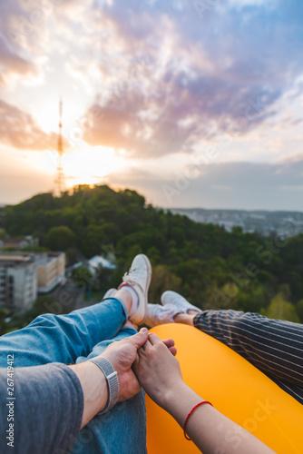 Fototapeta couple laying and enjoying view of sunset over the city obraz na płótnie