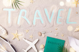 Travel sign on sand background with summer holidays, trip and vacation accessories. Flat lay style.