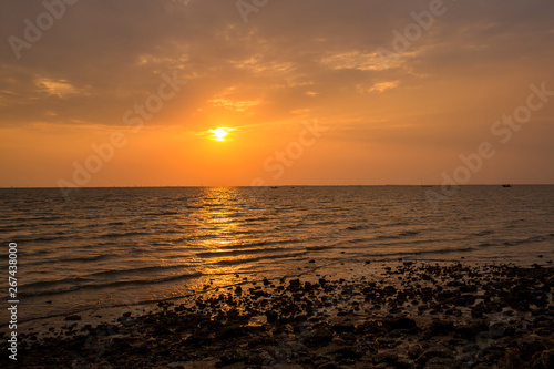 Bright sunset with large yellow sun under the sea surface. sunrise in the sea. Beautiful sunset above the sea. Tropical sunset on the beach.