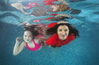 Girl and mom smims underwater in the swimming pool. Healthy family lifestyle and children water sports activity.