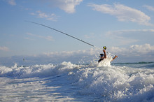 Surf Fisherman Into The Waves Trying To Cast The Line. Sea Fishing