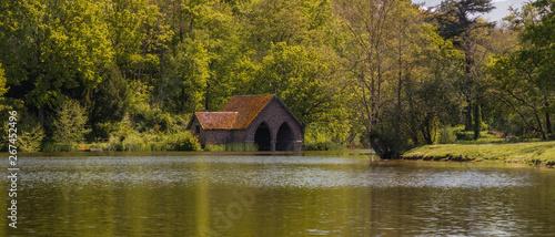 Foto Old brick boathouse on a lake.