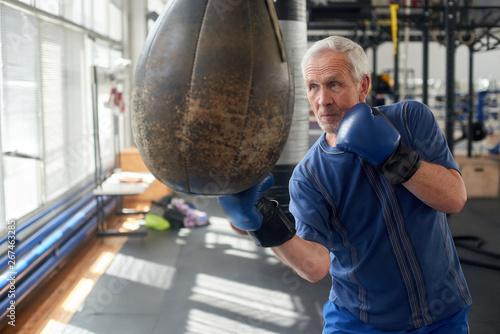 Fotomural  Elderly man hitting punching bag in boxing studio