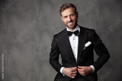 Carta da parati  Jolly groom standing and fixind his tuxedo